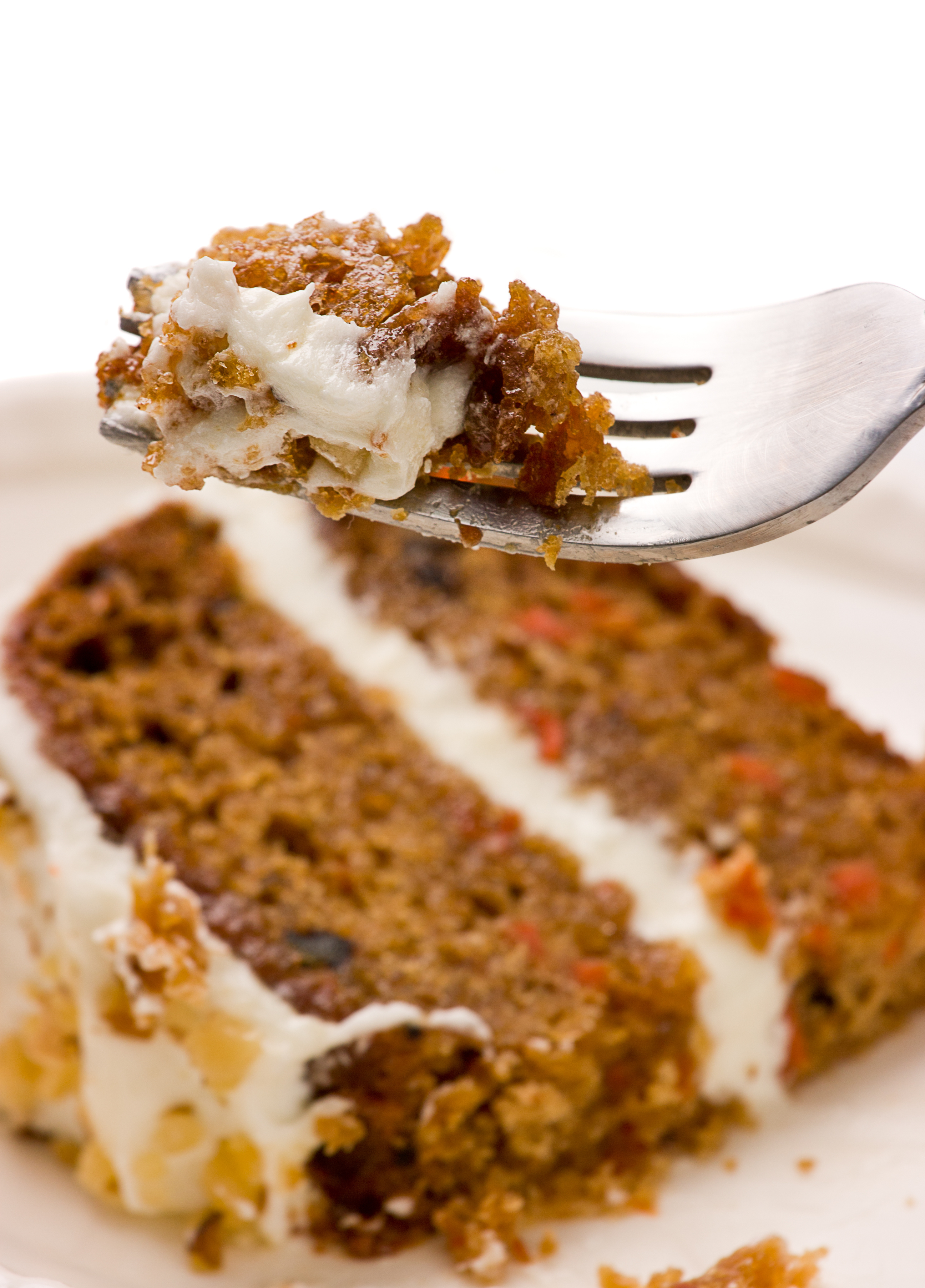Close up of  creamy sweet walnut carrot cake on a fork with white background.